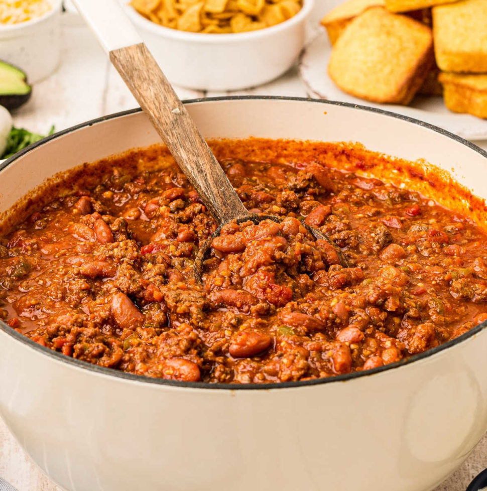 big white pot with deer chili inside with a spoon