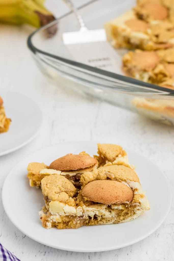 a close up of a banana brownie topped with vanilla wafers on a plate