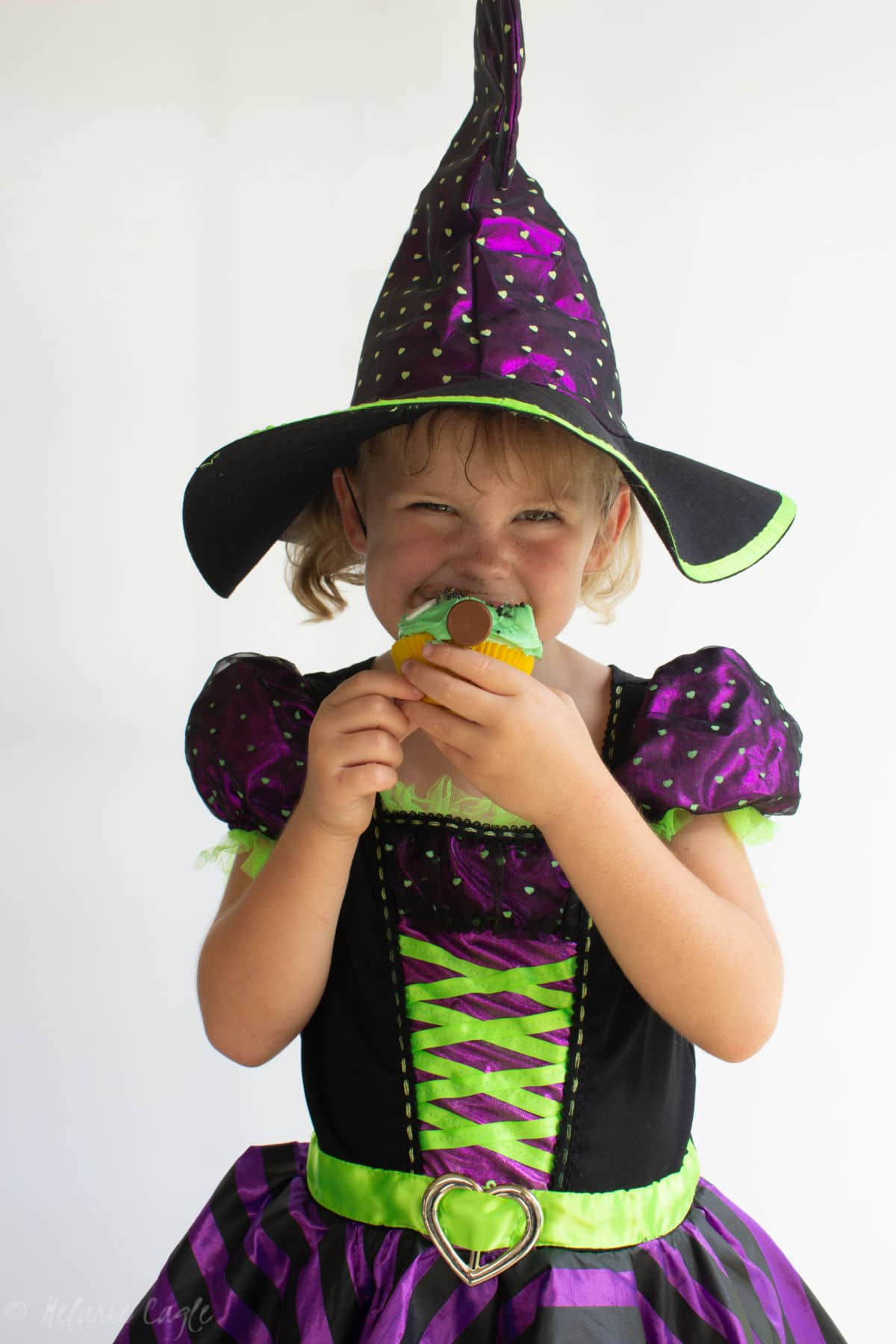 little girl wearing a witch costume for halloween eating a halloween cupcake