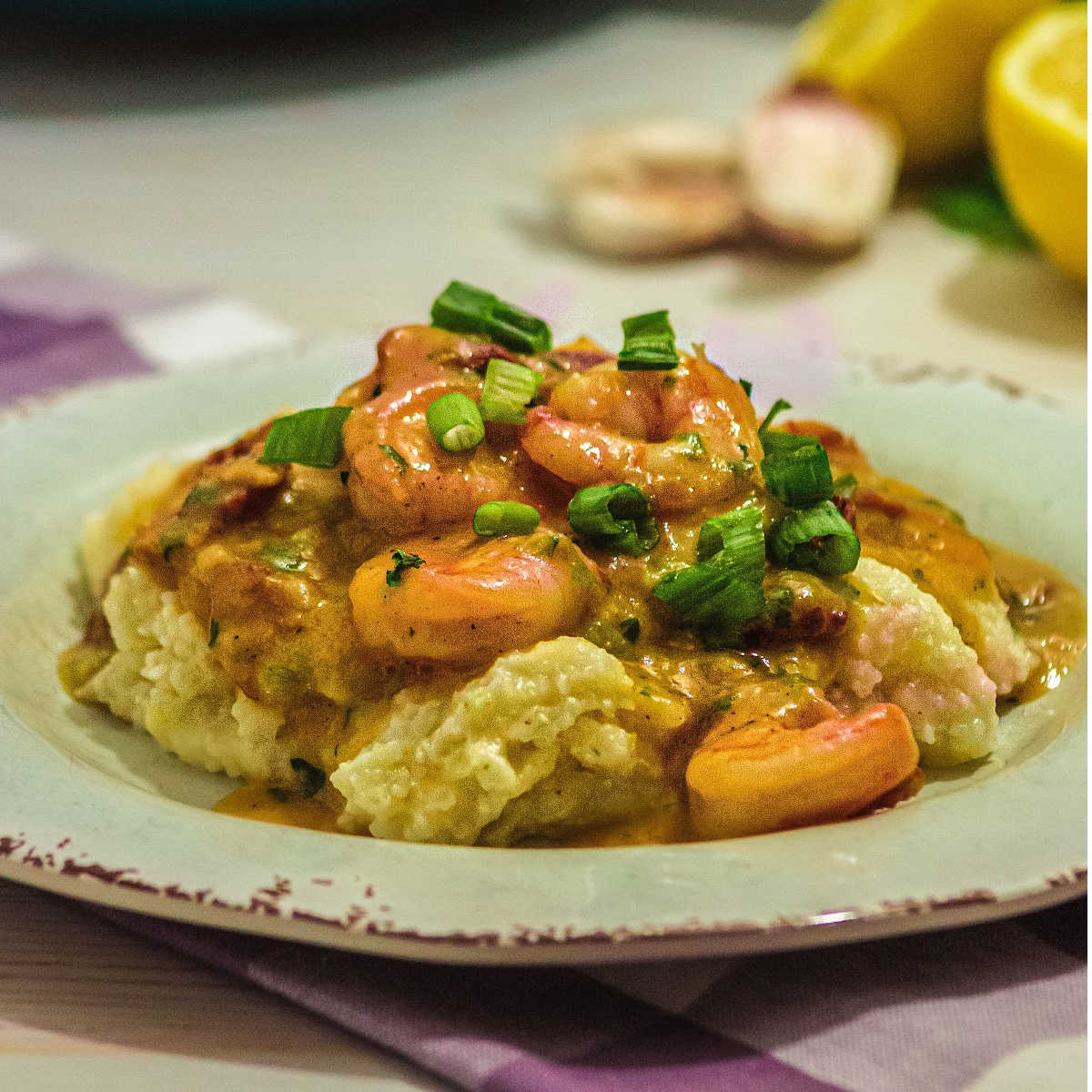 a plate of cheesy grits with some shrimp and bacon in a gravy poured over the top.