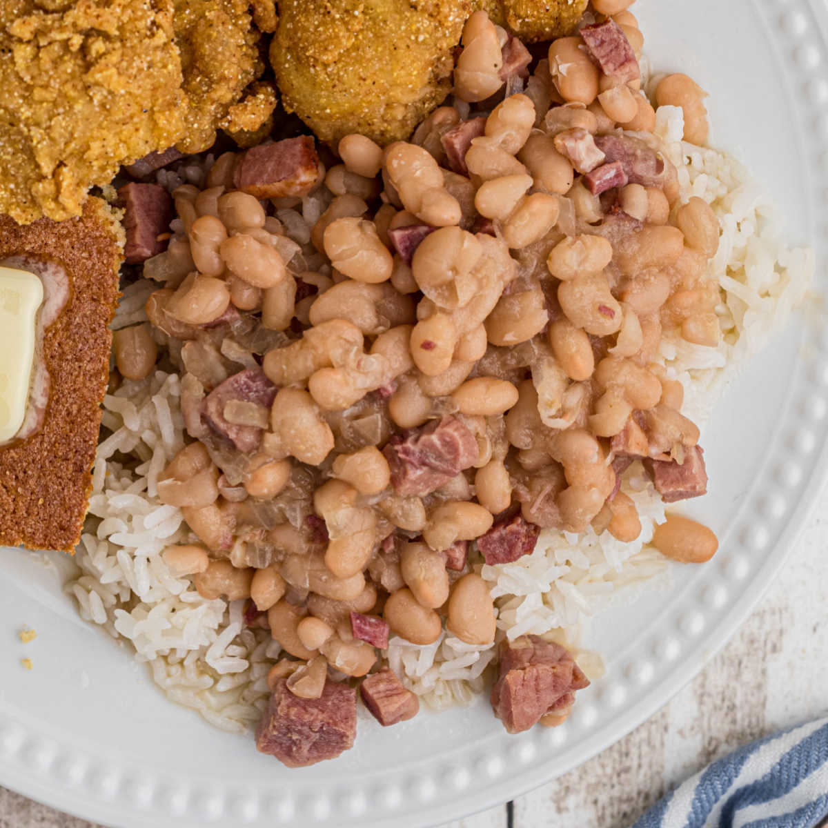 close up of white beans over rice on a plate with catfish peeking in
