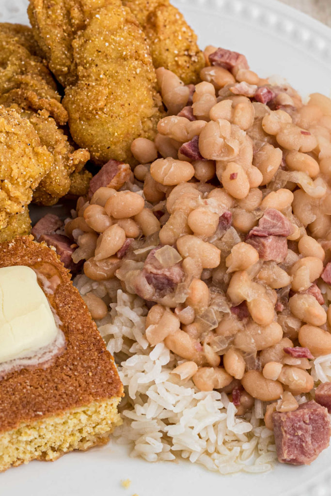 close up image of white beans on top of rice with catfish and cornbread peeking in