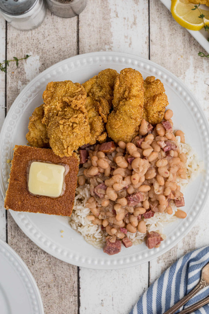 overhead shot of a plate of white beans and rice with fried catfish and cornbread