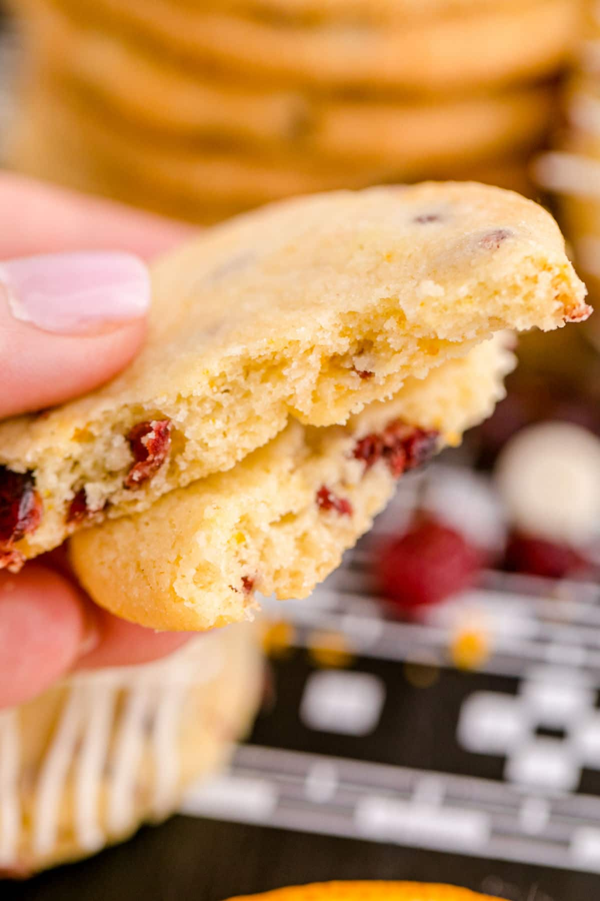 a cranberry orange shortbread cookie broken in half to see the inside of the cookie, close up