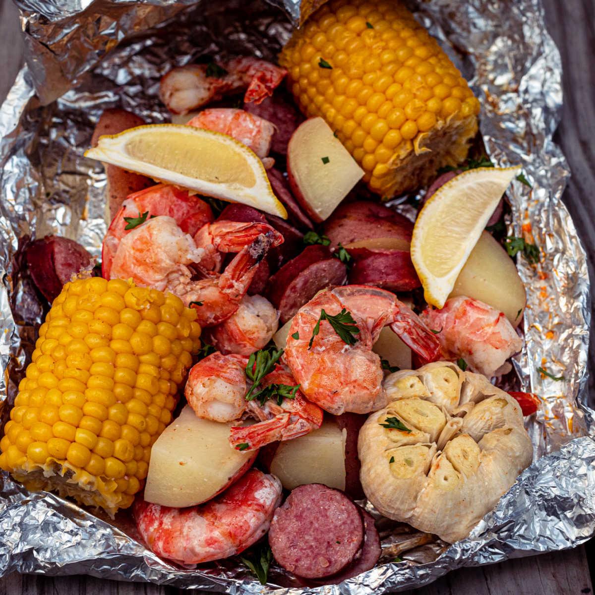 a foil packet full of shrimp, potatoes, garlic, corn and sausage
