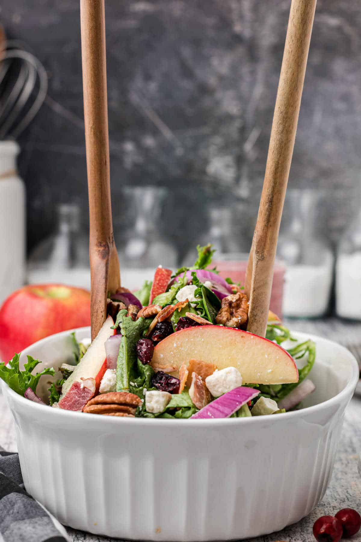 a wooden set of salad fork and spoon digging into a salad bowl