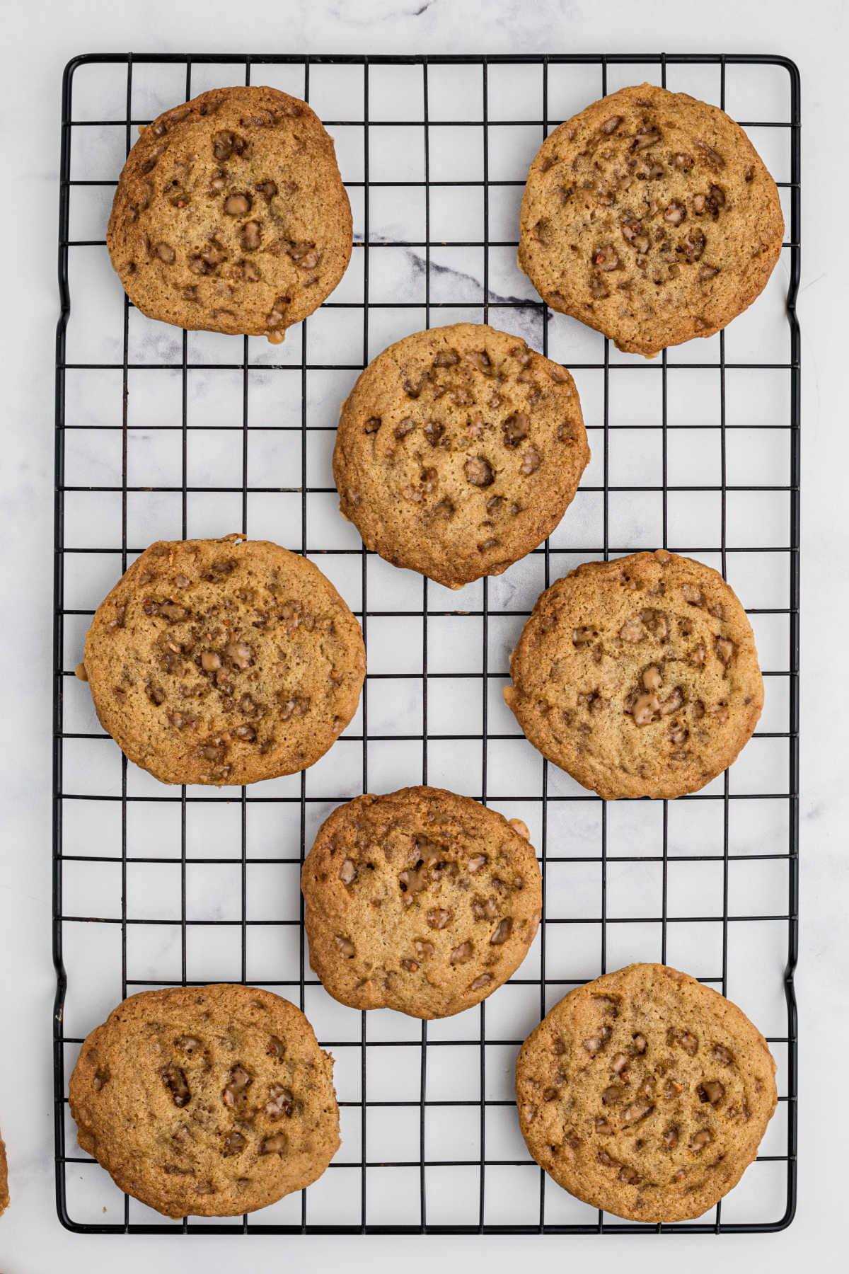 a cooling rack with cookies lined out